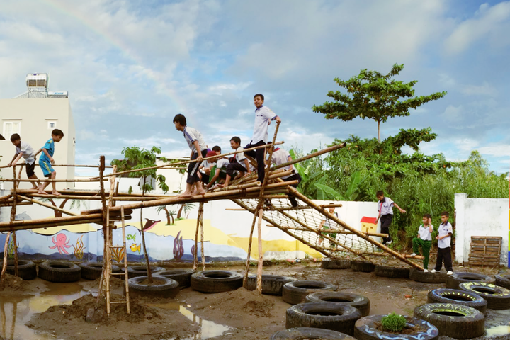 Image shows several children playing on a playground structure made from bamboo