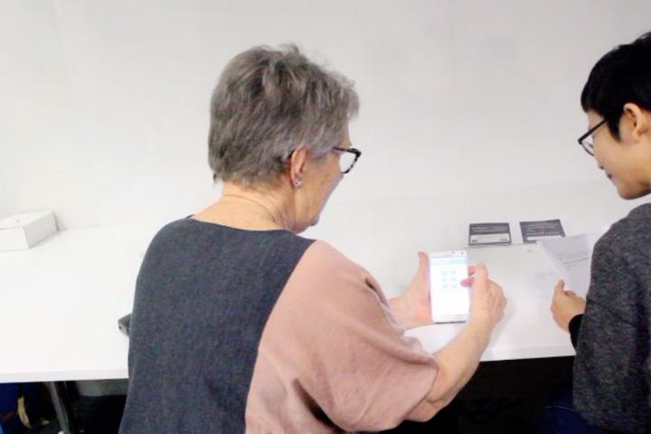 An older adult user sits on the left of the image, holding a smartphone with the Prospecfit app open in a think-aloud testing session. Researcher sits on the right, listening to what the user is saying.