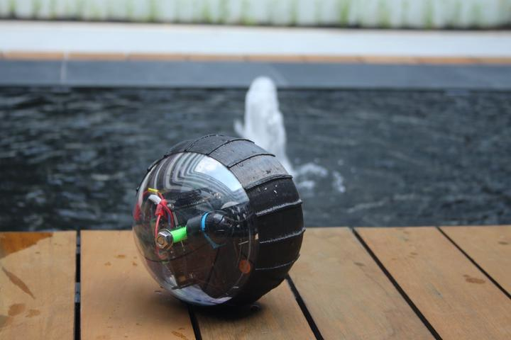 Image of Salamander, a spherical rolling robot, with a backdrop of a water fountain.